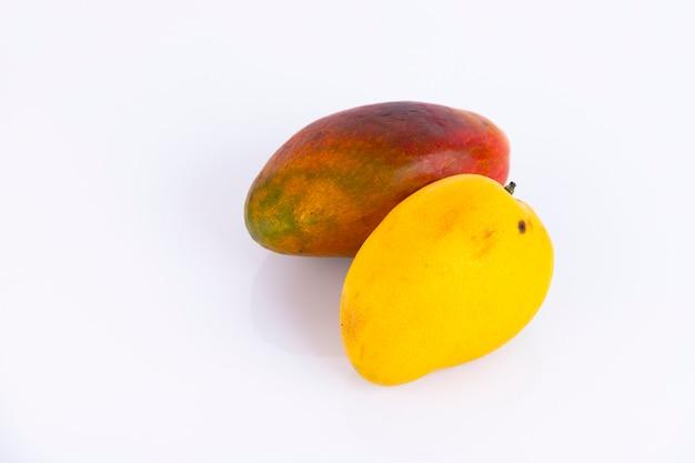 白い壁に、黄色と赤の皮をむいた様々な種類のマンゴー。スペースをコピーします。