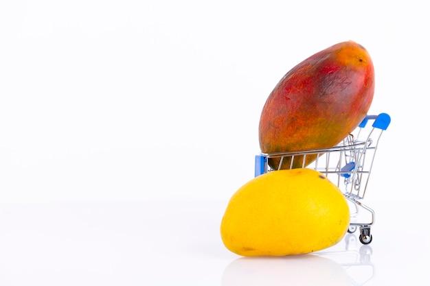 ショッピング カートの白い壁に黄色、赤い皮が付いたさまざまな種類のマンゴー。スペースをコピーします。