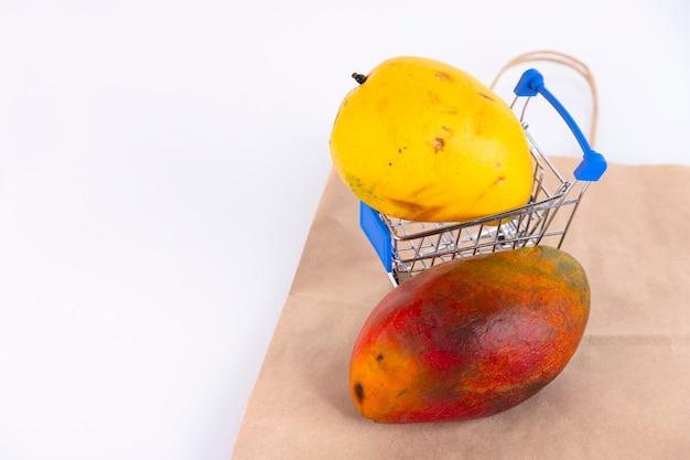 黄色と赤の果皮が入ったさまざまな種類のマンゴーがショッピング カートに入れられ、白い壁に紙袋が置かれています。スペースをコピーします。
