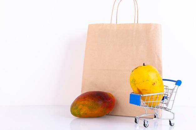 黄色と赤の果皮が入ったさまざまな種類のマンゴーがショッピング カートに入れられ、白い壁に紙袋が置かれています。スペースをコピーします。 Premium写真