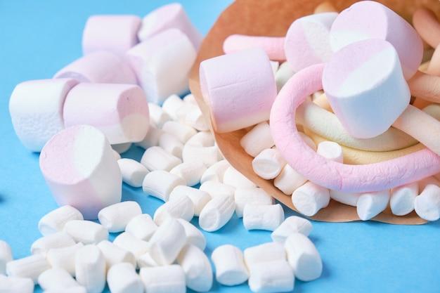 Различные виды зефира в бумаге на синем фоне, крупный план, экологически чистая упаковка конфет
