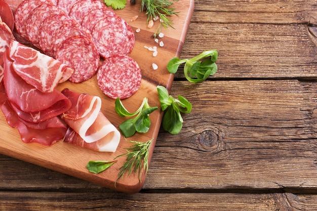 Различные виды мяса и колбас на деревянном столе