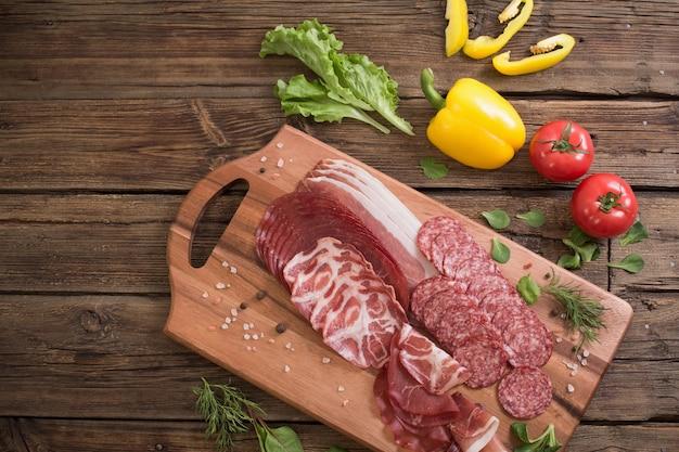 나무 테이블에 다양한 종류의 고기와 야채