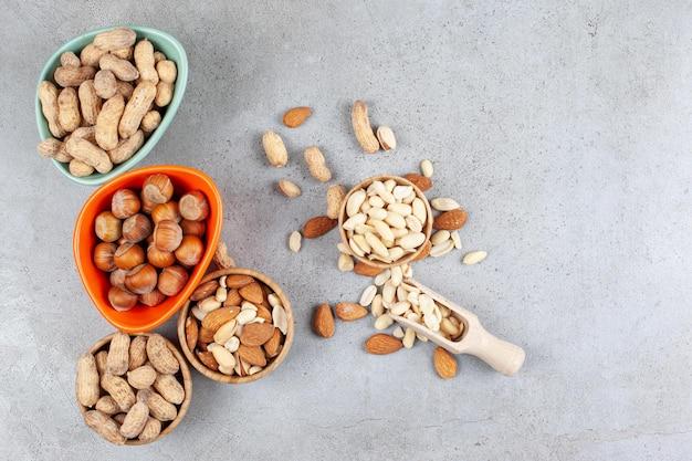 Различные виды орехов в мисках и разбросаны рядом с совком на мраморном фоне. фото высокого качества