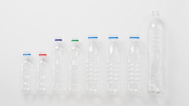Различные виды пластиковых бутылок на сером фоне
