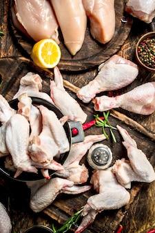 허브와 함께 다양한 종류의 생 닭고기. 나무 테이블에.