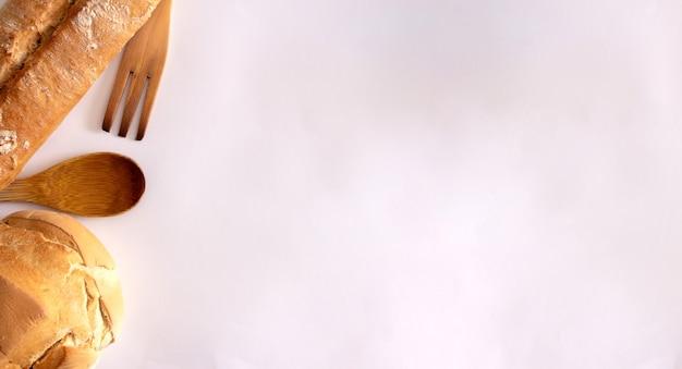 白い背景の上の木製のフォークとおたまとさまざまな種類の田舎のパンフラットレイコピースペース