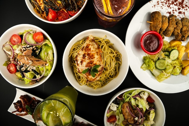 テーブルトップビューのさまざまな種類のサラダと料理