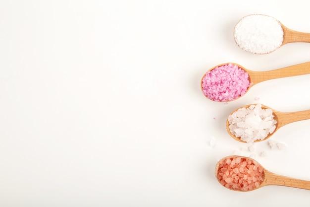 Различные типы морской соли спа в деревянных ложках, изолированных на белом фоне. вид сверху