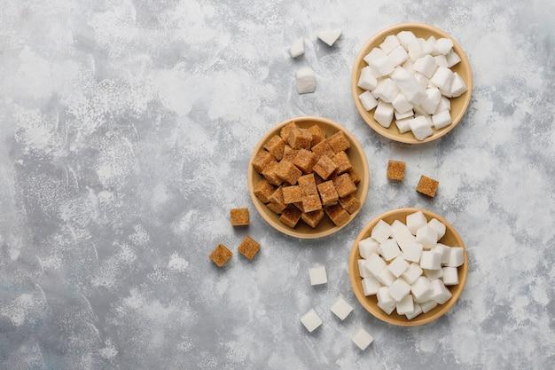 Различные виды сахара, коричневый сахар и белый на бетоне, вид сверху