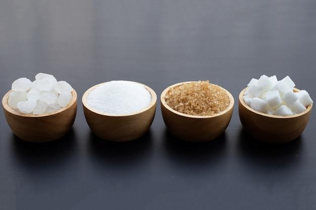 Различные виды сахара на темном фоне.