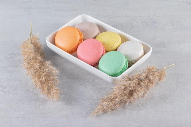 石のテーブルの上の白いボウルにさまざまな種類の甘いアーモンドケーキ。
