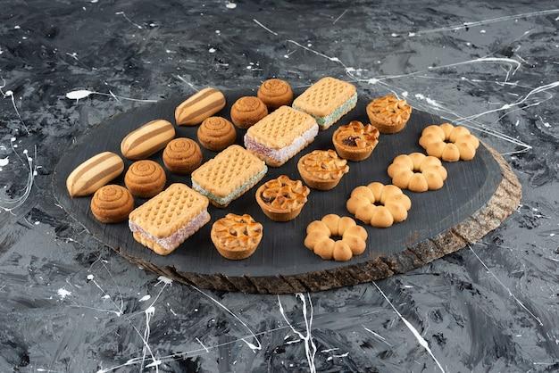 나무 조각에 다양한 종류의 달콤한 파이