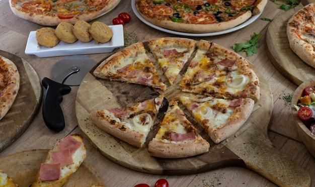 木製の背景にさまざまな種類のおいしいピザ。