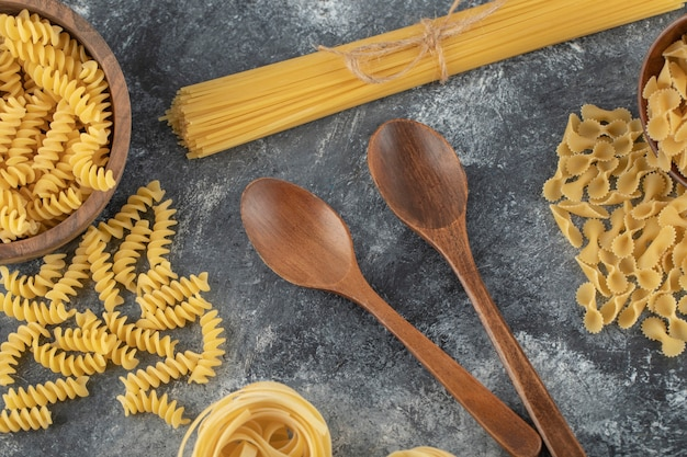 Различные виды сырых макарон с деревянными ложками.