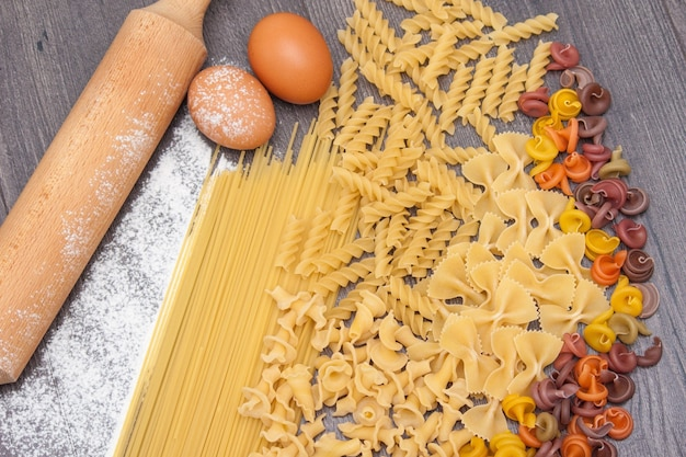 Various types or raw  pasta on the wooden background and ingredients for pasta eggs, flour