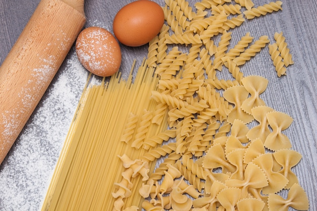 Various types or raw pasta on the wooden background and ingredients for pasta eggs, flour.