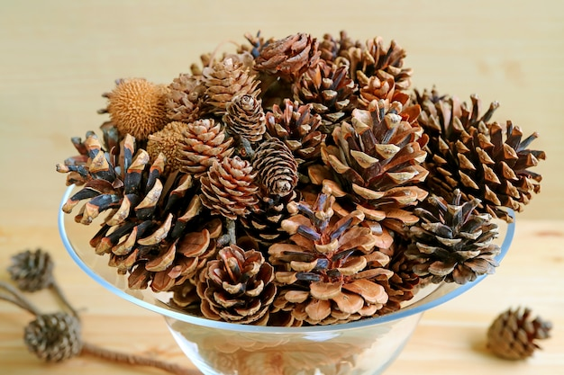 Various types and sizes of many natural dry pine cones in a glass compote on wooden background