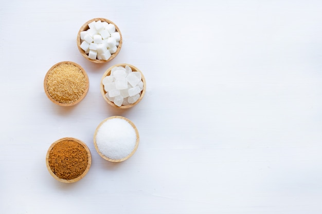 Various types of sugar on white wooden background.