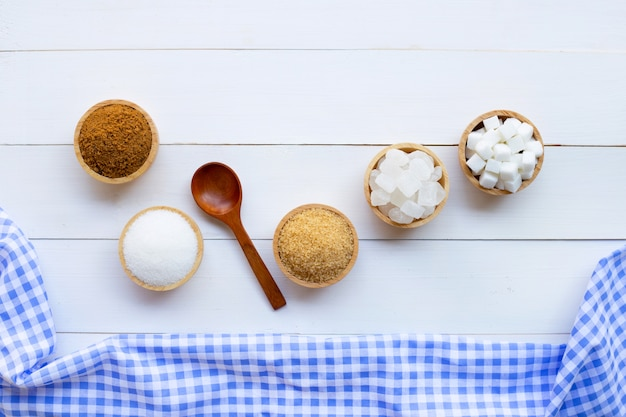 Various types of sugar on wooden background.