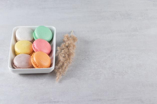 Vari tipi di torte di mandorle dolci in una ciotola bianca sul tavolo di pietra.