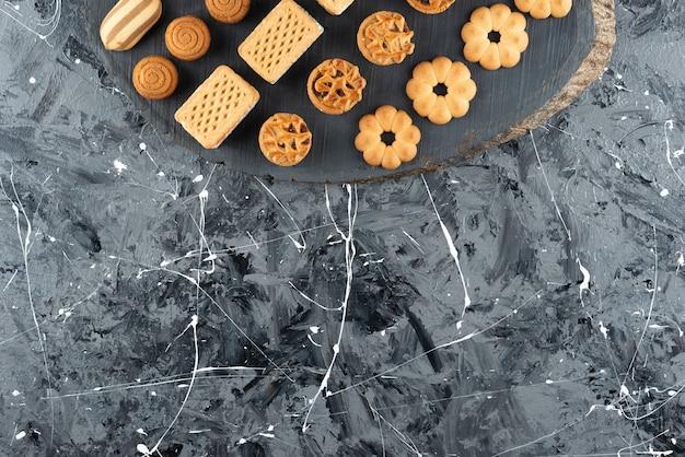Vari tipi di pasticceria dolce su un pezzo di legno.
