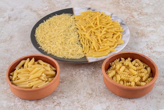 Vari tipi di maccheroni crudi su un bel piatto