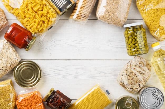 Различные сырые крупы, зерна, макаронные изделия и консервы на белом деревянном столе. ингредиенты для приготовления. фон рамки с копией пространства.