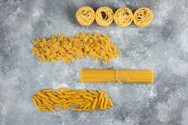 Various uncooked pasta on stone.