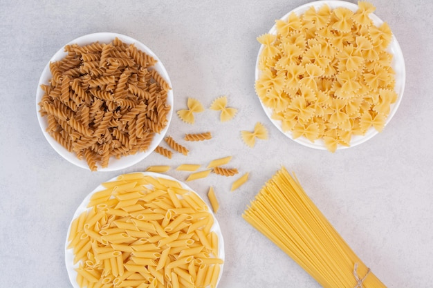 Various uncooked pasta on white table.