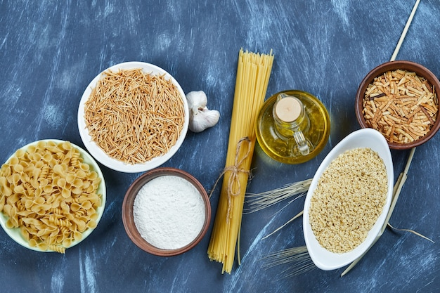 Various uncooked pasta with a bottle of oil, flour and garlic.
