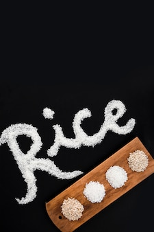 Various uncooked rice on wooden tray with text on black backdrop