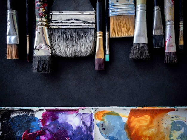 다양한 사용 아티스트 페인트 브러시 많은 크기와 어두운 표면에 고립 된 더러운 팔레트