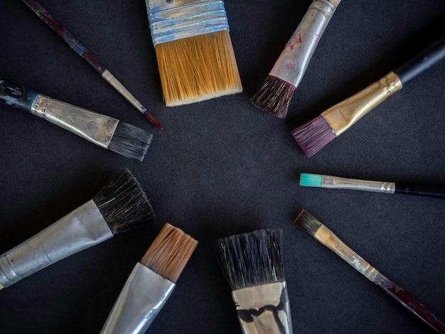 다양한 사용 아티스트 페인트 브러시 많은 크기가 어두운 표면에 고립 된 원으로 정렬