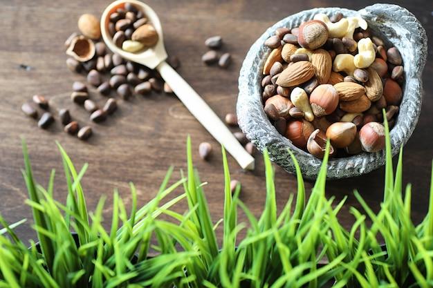 나무 탁자에 있는 다양하고 유용하고 맛있는 견과류와 푸른 풀이 있는 냄비