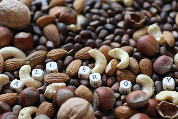 Various useful and tasty nuts on a wooden table and pots with green grass