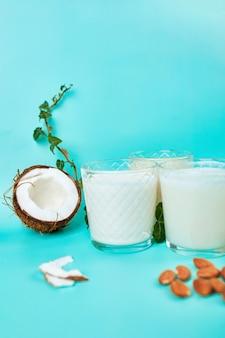 다양한 채식주의 식물 기반 우유 및 재료, 비 유제품 우유, 복사 공간이있는 파란색 벽에 안경에있는 대체 유형의 채식주의 우유