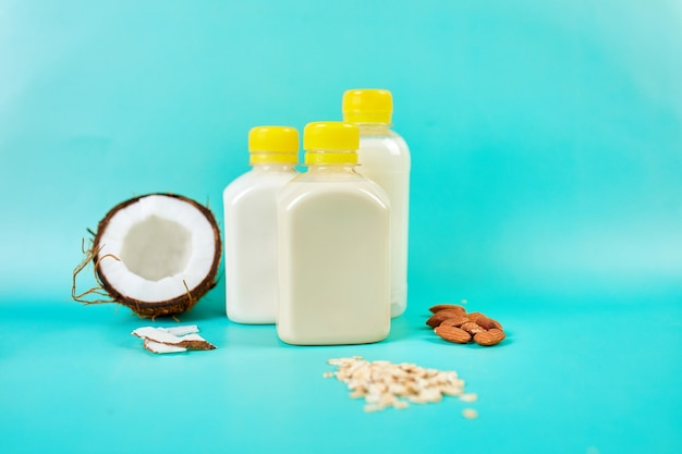 Various vegan plant based milk and ingredients, non-dairy milk, alternative types of vegan milks in bottle on a blue background with copy space