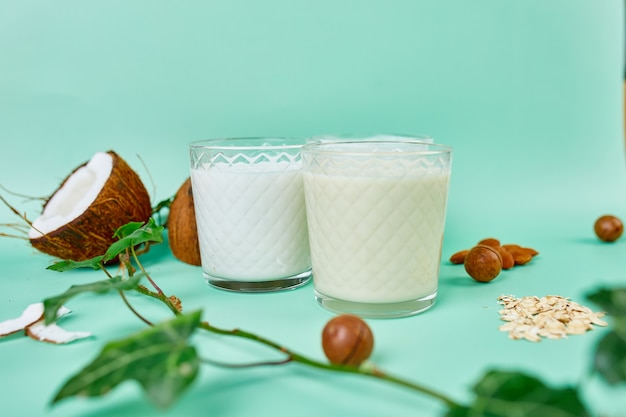 Various vegan plant based milk and ingredients, non-dairy milk, alternative types of vegan milks in glasses on a blue background with copy space