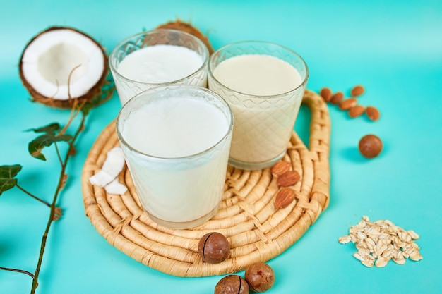 Various vegan plant based milk and ingredients, non-dairy milk, alternative types of vegan milks in glasses on a blue surface with copy space