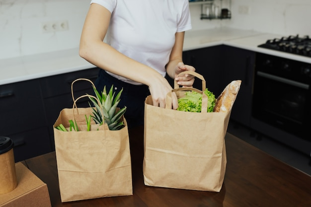 Различные овощи и фрукты в бумажных пакетах, которые молодая девушка разбирает дома на кухонном столе.