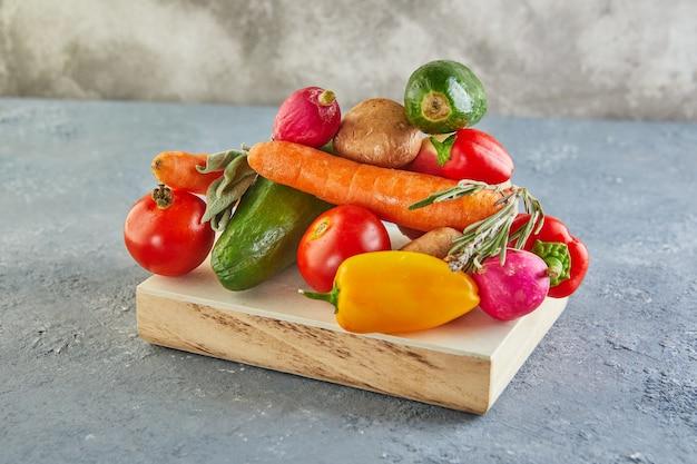 Различные овощи и фрукты, лежащие на деревянном подиуме, на серо-голубом фоне