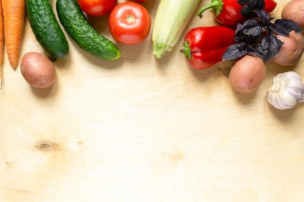明るい木製の背景にさまざまな野菜やハーブ。テキスト用のスペース。