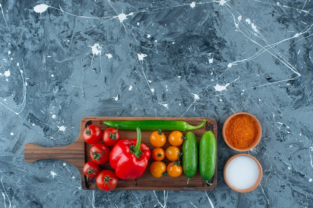 Various vegetables on a board next to salt and spice, on the marble background.