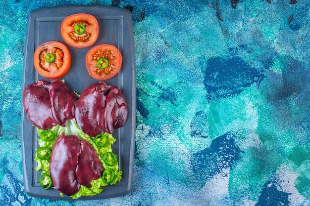 Varie verdure e fegatini di pollo sul vassoio di legno