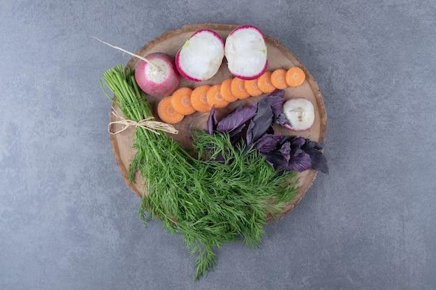 大理石の表面に、ボードに入ったさまざまな野菜。