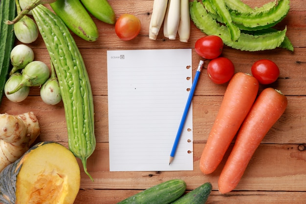 Various vegetables with blank note page and pencil on wooden background. top view