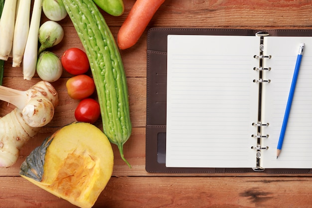 Various vegetables with blank notebook and pencil on wooden background. top view