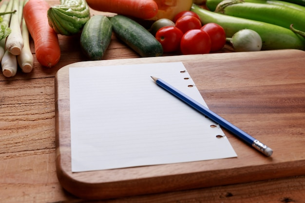 Various vegetables with blank notebook and pencil on wooden background.