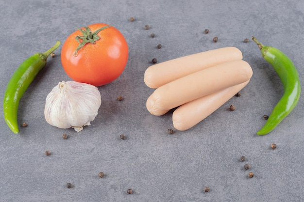Various vegetables with sausages on marble surface